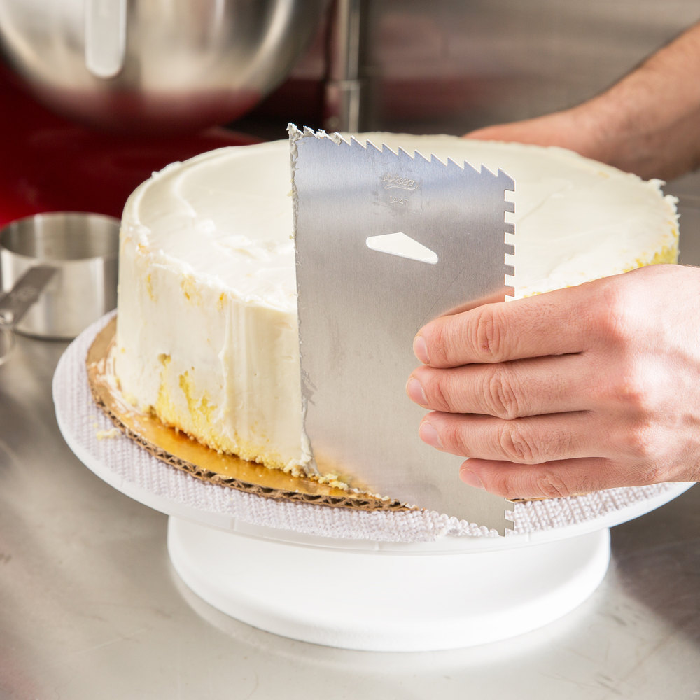 Run the icing smoother along the sides of the cake. Photo Credit: Webstaurant Store